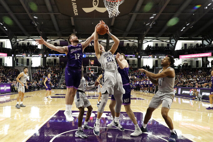 Penn State forward John Harrar (21) battles for a rebound against Northwestern guard Pat Spencer, left, and center Ryan Young during the first half of an NCAA college basketball game in Evanston, Ill., Saturday, March 7, 2020. (AP Photo/Nam Y. Huh)