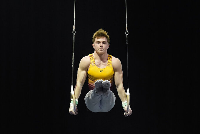 """Michael Moran, representing the University of Minnesota, competes during the Winter Cup gymnastics competition, Sunday, Feb. 28, 2021, in Indianapolis.  A junior from Morristown, New Jersey, Moran admits there were people within his inner circle who discouraged him from competing collegiately because they viewed his chosen sport as a """"dying entity."""" The University of Minnesota and the University of Iowa will stop offering it as a scholarship sport at the end of the month. (AP Photo/Darron Cummings)"""