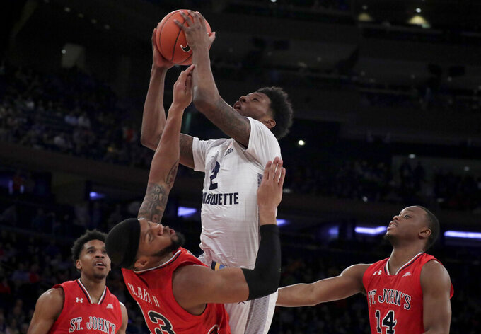Marquette forward Sacar Anim, center, goes up for a shot against St. John's forward Marvin Clark II (13) during the first half of an NCAA college basketball game in the Big East men's tournament, Thursday, March 14, 2019, in New York. St. John's Justin Simon (5) and Mustapha Heron (14) look on during the play. (AP Photo/Julio Cortez)