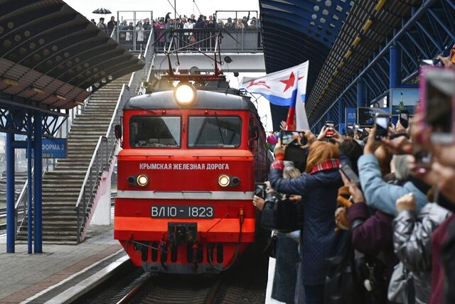 People celebrate the arrival of the train from Russia in Sevastopol, Crimea, after it crossed a bridge linking Russia and the Crimean peninsula on Wednesday, Dec. 25, 2019. Ukrainian officials opened a criminal probe Wednesday after a passenger train from Russia arrived in Crimea via a new Russian-built bridge, arguing that the train illegally carried people across the Ukrainian border. (AP Photo)