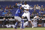 Miami Marlins' Lewis Brinson, right, scores past Kansas City Royals catcher Nick Dini on a single hit by Miguel Rojas during the fourth inning of a baseball game Sunday, Sept. 8, 2019, in Miami. (AP Photo/Lynne Sladky)