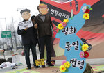 Protesters wearing masks of U.S. President Donald Trump and North Korean leader Kim Jong Un stand near the map of Korean Peninsula during a rally demanding the denuclearization of the Korean Peninsula and peace treaty near the U.S. embassy in Seoul, South Korea, Thursday, March 21, 2019. The Korean Peninsula remains in a technical state of war because the 1950-53 Korean War ended with an armistice, not a peace treaty. More than 20 protesters participated at a rally and also demanding the end the Korean War and to stop the sanction on North Korea. The letters read