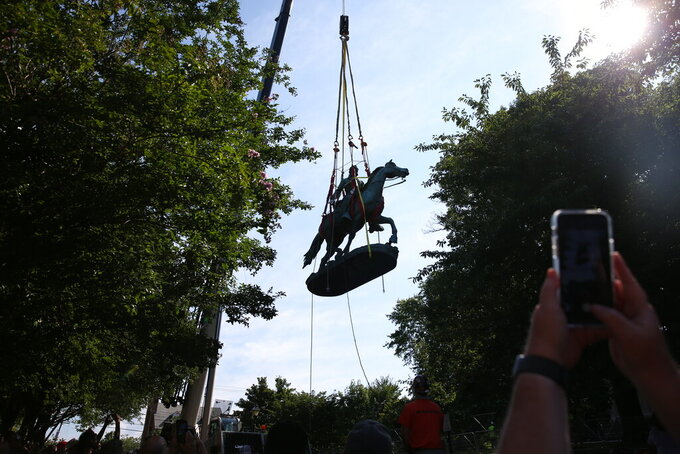 """The monument of Stonewall Jackson is lifted from its pedestal on Saturday, July 10, 2021 in Charlottesville, Va.   The removal of the Lee and Jackson statues comes nearly four years after violence erupted at the infamous """"Unite the Right"""" rally.  (Erin Edgerton/The Daily Progress via AP)"""
