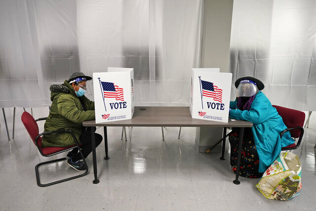 FILE - In this Oct. 6, 2020, file photo two voters fill out ballots during early voting at the Cuyahoga County Board of Elections in Cleveland. A surge in coronavirus cases is hitting key presidential battleground states a little more than two weeks before Election Day, raising concerns that voting could be thrown into chaos despite months of preparation and planning by election officials and voters. (AP Photo/Tony Dejak, File)