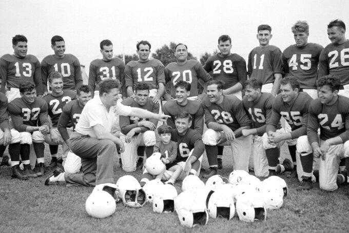 FILE - In this July 26, 1939, file photo, Philadelphia Eagles owner and head coach Bert Bell talks to his squad as his son, Bert Bell Jr. sits on a players lap, in Philadelphia. Bell, who later became the league's commissioner, created the NFL draft as a way to assist teams who couldn't attract top talent in the free-for-all system that had been in place. (AP Photo/File)