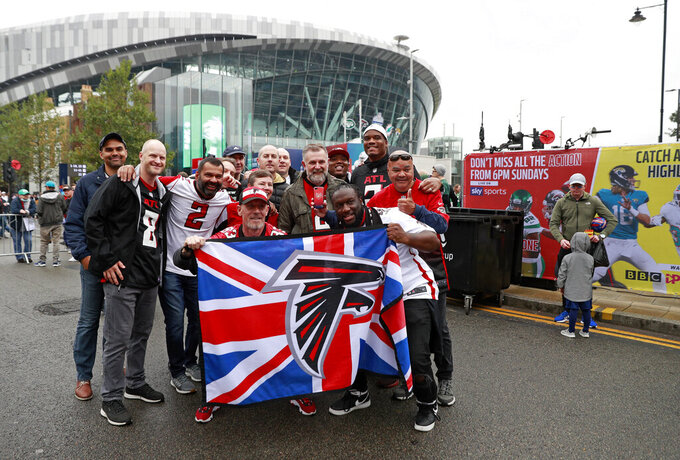 Fans gather outside the stadium before NFL football game between the New York Jets and the Atlanta Falcons at the Tottenham Hotspur stadium in London, England, Sunday, Oct. 10, 2021. (AP Photo/Ian Walton)