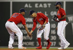 Boston Red Sox's Mookie Betts celebrates with Rafael Devers (11) as Jackie Bradley Jr. stands next to them after a 16-4 win in the team's baseball game against the Los Angeles Angels at Fenway Park, Friday, Aug. 9, 2019, in Boston. (AP Photo/Elise Amendola)
