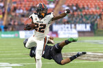 Oregon State running back Jermar Jefferson (22) looks for the end zone after hurdling Hawaii defensive back Kalen Hicks (3) during the first half of an NCAA college football game, Saturday, Sept. 7, 2019, in Honolulu. (AP Photo/Eugene Tanner)