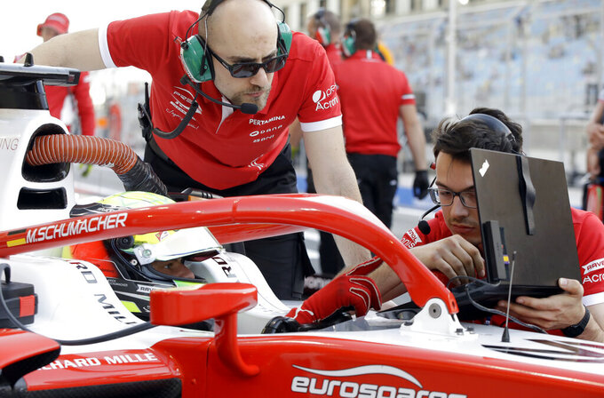 Formula 2 driver Mick Schumacher, left, speaks to mechanics as he prepares for the Formula 2 qualifying session at the Bahrain International Circuit in Sakhir, Bahrain, Friday, March 29, 2019. It promises to be a whirlwind few days for the son of Formula One great Michael Schumacher, as he makes his F2 debut this weekend and then drives in his first F1 test for Ferrari on Tuesday. (AP Photo/Luca Bruno)