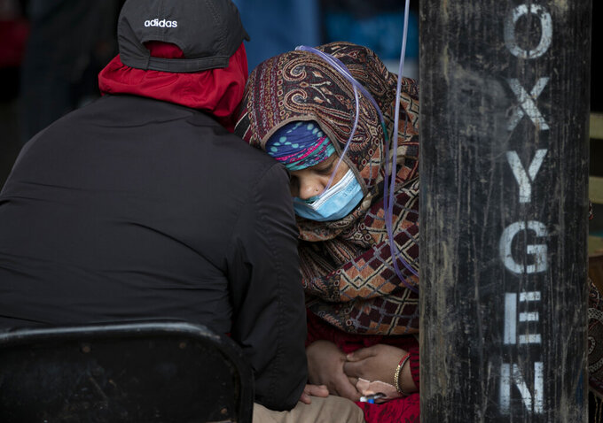 A COVID-19 patient receives oxygen outside an emergency ward at a government run hospital in Kathmandu, Nepal, Thursday, May 13, 2021. (AP Photo/Niranjan Shrestha)