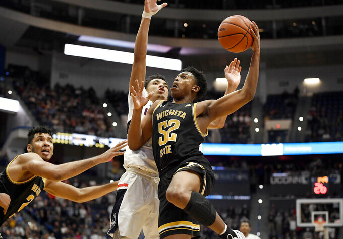 Wichita State's Grant Sherfield, right, goes up for a basket against Connecticut's James Bouknight, back center, in the first half of an NCAA college basketball game, Sunday, Jan. 12, 2020, in Hartford, Conn. (AP Photo/Jessica Hill)
