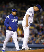 FILE - In this Friday, May 11, 2018, file photo, Los Angeles Dodgers manager Dave Roberts, left, walks to the mound to remove starting pitcher Kenta Maeda during the fifth inning of a baseball game against the Cincinnati Reds in Los Angeles. One-quarter of the way into the season, the defending NL champion are off to their worst start in 60 years. Lately they're even losing to bad teams. (AP Photo/Mark J. Terrill, File)