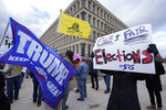 Protesters stand outside the Richard H. Austin state office building during a rally in Lansing, Mich., Saturday, Nov. 14, 2020. Michigan's elections board is meeting to certify the state's presidential election results. (AP Photo/Paul Sancya)