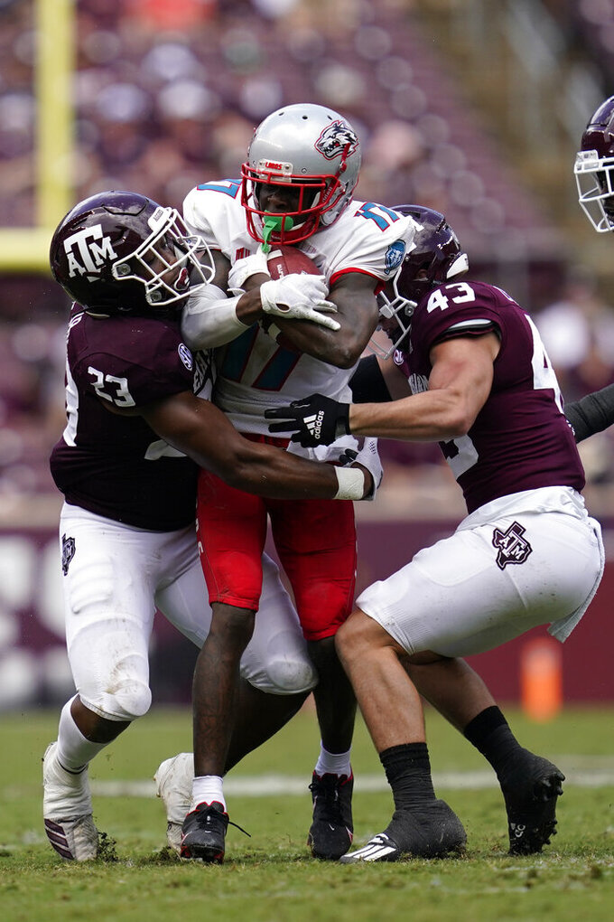 New Mexico wide receiver Mannie Logan-Greene (17) is tackled after a short gain by Texas A&M linebacker Tarian Lee Jr. (23) and defensive back Alex Zettler (43) during the second half of an NCAA college football game on Saturday, Sept. 18, 2021, in College Station, Texas. (AP Photo/Sam Craft)