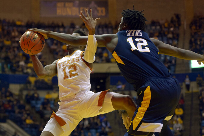 Texas guard Kerwin Roach II (12) is blocked by West Virginia forward Andrew Gordon (12) during the first half of an NCAA college basketball game in Morgantown, W.Va., Saturday, Feb. 9, 2019. (AP Photo/Craig Hudson)