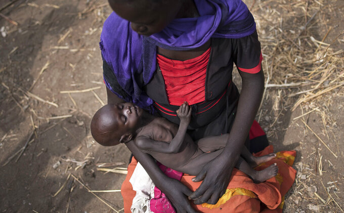 """FILE - In this April 5, 2017, file photo, Adel Bol, 20, cradles her 10-month-old daughter Akir Mayen at a food distribution site in Malualkuel, in the Northern Bahr el Ghazal region of South Sudan. The United Nations humanitarian office said Wednesday, Nov. 18, 2020 it is releasing $100 million in emergency funding to seven countries at risk of famine in Africa and the Middle East amid conflict and the COVID-19 pandemic, while the humanitarian chief says returning to a world where famines are common would be """"obscene."""" (AP Photo, File)"""