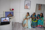 Aagna Patel, 16, Pushpa Patel, 68, Hemali Patel 42, dressed in their best saris, watch Guru Pujya Swayamprakashdas speak to them through their television screen in the comfort of their living room in their suburban home in Hemel Hempstead, England, on Sunday, June 14, 2020.