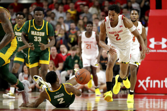 Maryland guard Aaron Wiggins, right, tries to control the ball as George Mason guard Xavier Johnson falls to the floor during the second half of an NCAA college basketball game Friday, Nov. 22, 2019, in College Park, Md. Maryland won 86-63. (AP Photo/Julio Cortez)