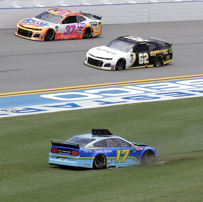 Ricky Stenhouse Jr. (17) slides backwards after making contact with another car coming out of Turn 4 as Brendan Gaughan (62) and Chris Buescher (37) go past during a NASCAR Cup Series auto race at Daytona International Speedway, Sunday, July 7, 2019, in Daytona Beach, Fla. (AP Photo/John Raoux)