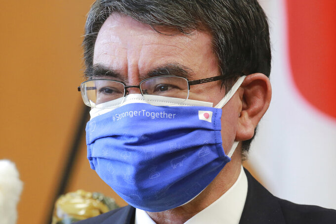 Japanese Vaccine Minister Taro Kono wearing a face mask with flags of Japan and EU, left, on it speaks during an interview in Tokyo, Monday, March 29, 2021. Kono tasked with COVID-19 vaccinations urged the EU to ensure stable shipment of Pfizer vaccines amid distribution uncertainty in a country where the Olympics are coming up in four months. (AP Photo/Koji Sasahara)