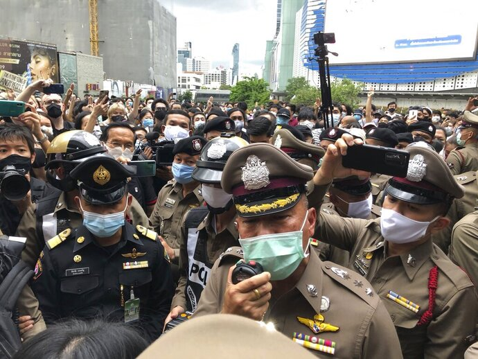A police officer tries to speak to a crowd at an anti-government gathering Saturday, Aug. 8, 2020, in Bangkok, Thailand. Political tensions are rising in Thailand as pro-democracy activists vowed to step up protests against the government and police arrested some key figures in recent demonstrations. (AP Photo/Jerry Harmer)