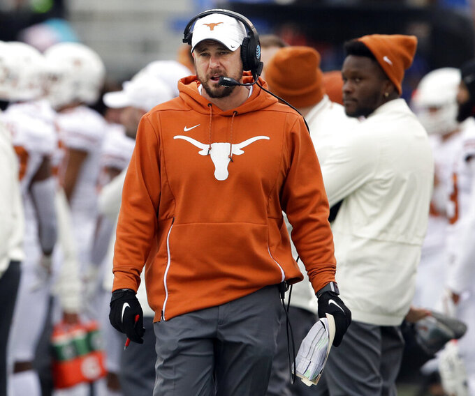 FILE - In this Nov. 23, 2018, file photo, Texas head coach Tom Herman works the sideline during the first half of an NCAA college football game against Kansas, in Lawrence, Kan.  Herman and LSU head coach Ed Orgeron like the colors they'll be wearing Saturday night when No. 6 Tigers meet No. 9 Texas in one of the top non-conference matchups of the 2019 season. (AP Photo/Orlin Wagner)