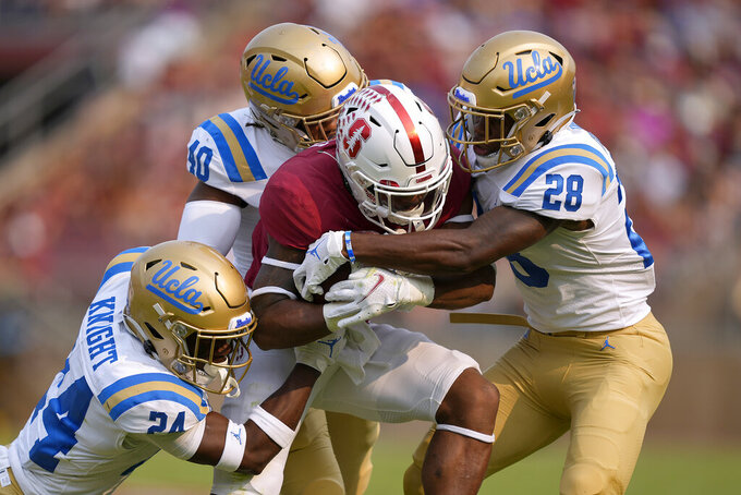 Stanford running back Nathaniel Peat (8) is stopped by UCLA defensive back Qwuantrezz Knight (24), linebacker Ale Kaho (10) and defensive back Kenny Churchwell III (28) during the first half of an NCAA college football game Saturday, Sept. 25, 2021, in Stanford, Calif. (AP Photo/Tony Avelar)