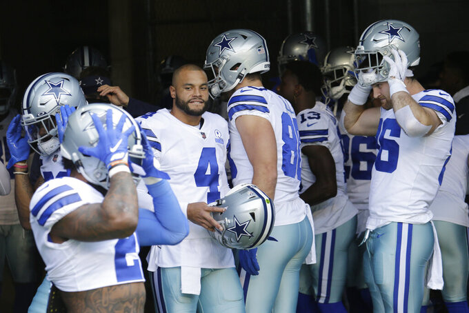 Dallas Cowboys quarterback Dak Prescott (4) stands with teammates in the tunnel before warmups prior to an NFL football game against the Seattle Seahawks, Sunday, Sept. 27, 2020, in Seattle. (AP Photo/John Froschauer)