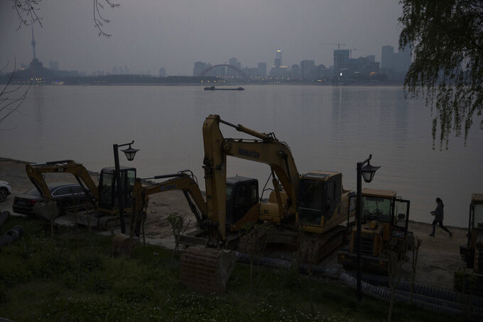 In this April 4, 2020, photo, a resident wearing a mask against the new coronavirus walks past idling digging machineries along the Yangtze River in Wuhan in central China's Hubei province. When the Chinese city of Wuhan is at last released from virus quarantine Wednesday, it will be like awakening from a persistent slumber. Over the 76 days of lockdown, the city has at times lived in a crepuscular world of neither night or day, where time seems to pass more slowly and one day blurs into the next. (AP Photo/Ng Han Guan)