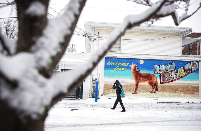 A pedestrian walk through the snow past a mural, Tuesday, Dec. 3, 2019, in Providence, RI. (AP Photo/David Goldman)