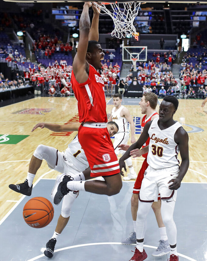 Bradley's Luqman Lundy, left, dunks as Loyola of Chicago's Aher Uguak (30) watches during the first half of an NCAA college basketball game in the semifinal round of the Missouri Valley Conference tournament, Saturday, March 9, 2019, in St. Louis. (AP Photo/Jeff Roberson)