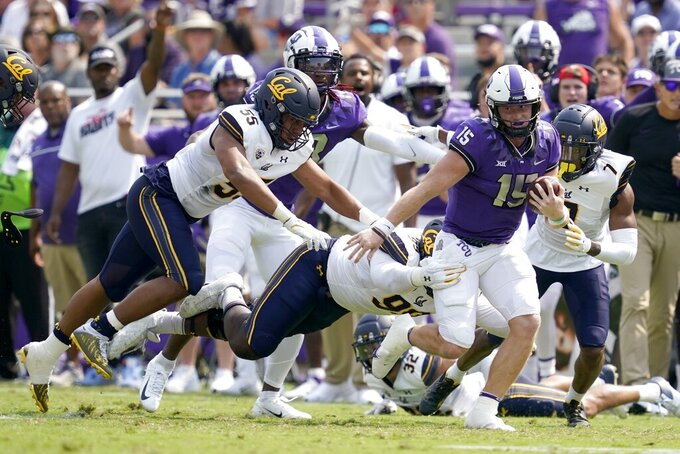 TCU quarterback Max Duggan (15) attempts to escape being tackled by California linebacker Mo Iosefa (55), Ethan Saunders (99) and Chigozie Anusiem (7) after a short gain in the first half of an NCAA college football game in Fort Worth, Texas, Saturday, Sept. 11, 2021. (AP Photo/Tony Gutierrez)