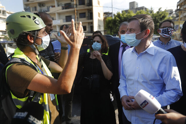 U.S. Undersecretary of State for Political Affairs David Hale, right, listens to an NGO volunteer during his visit to a main gathering point for volunteers, near the site of last week's explosion that hit the seaport of Beirut, Lebanon, Thursday, Aug. 13, 2020. (AP Photo/Hussein Malla, Pool)