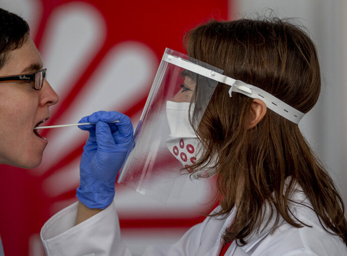 For demonstration purposes, an employee of the Centogene company takes a throat swab from a colleague at the airport in Frankfurt, Germany, Monday, June 29, 2020. In the future, people will be able to be tested for the corona virus within a few hours at Germany's first