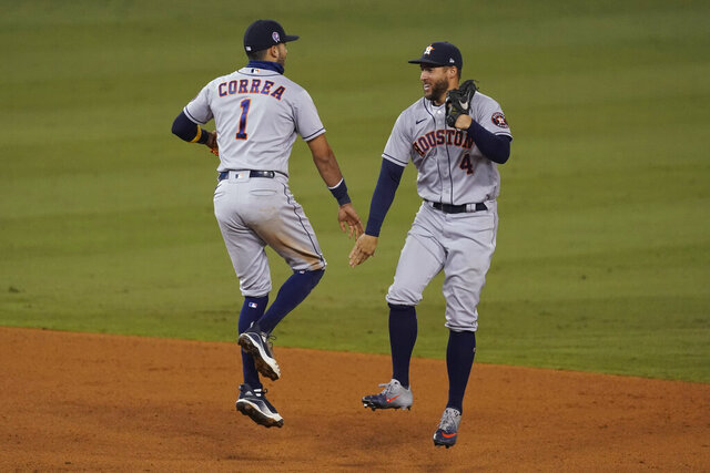 Houston Astros shortstop Carlos Correa (1) and center fielder George Springer (4) celebrate the team's 7-5 win over the Los Angeles Dodgers in a baseball game at Dodger Stadium on Saturday, Sept. 12, 2020, in Los Angeles. (AP Photo/Ashley Landis)