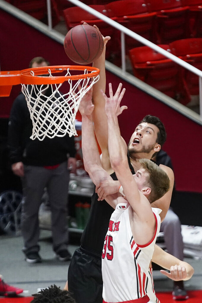 Oregon State center Roman Silva, rear, dunks on Utah center Branden Carlson (35) during the first half of an NCAA college basketball game Wednesday, March 3, 2021, in Salt Lake City. (AP Photo/Rick Bowmer)