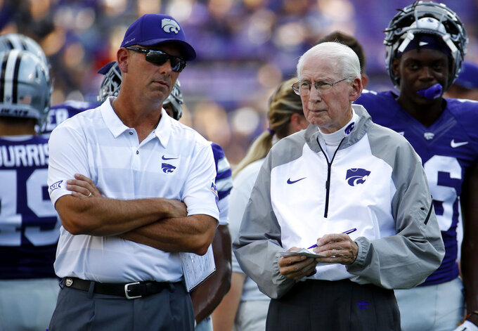 FILE - In this Sept. 1, 2018, file photo, Kansas State head coach Bill Snyder talks with his son and special teams coordinator Sean Snyder before an NCAA college football game against the South Dakota, in Manhattan, Kan. Snyder said again this week that he will evaluate after the season whether he will return next year, but there has been growing unrest in the program. Many believe that Snyder, who prefers that his son and special teams coordinator Sean eventually replaces him, will retire after this year. The question then becomes whether Snyder will get his wish.(AP Photo/Charlie Riedel, File)