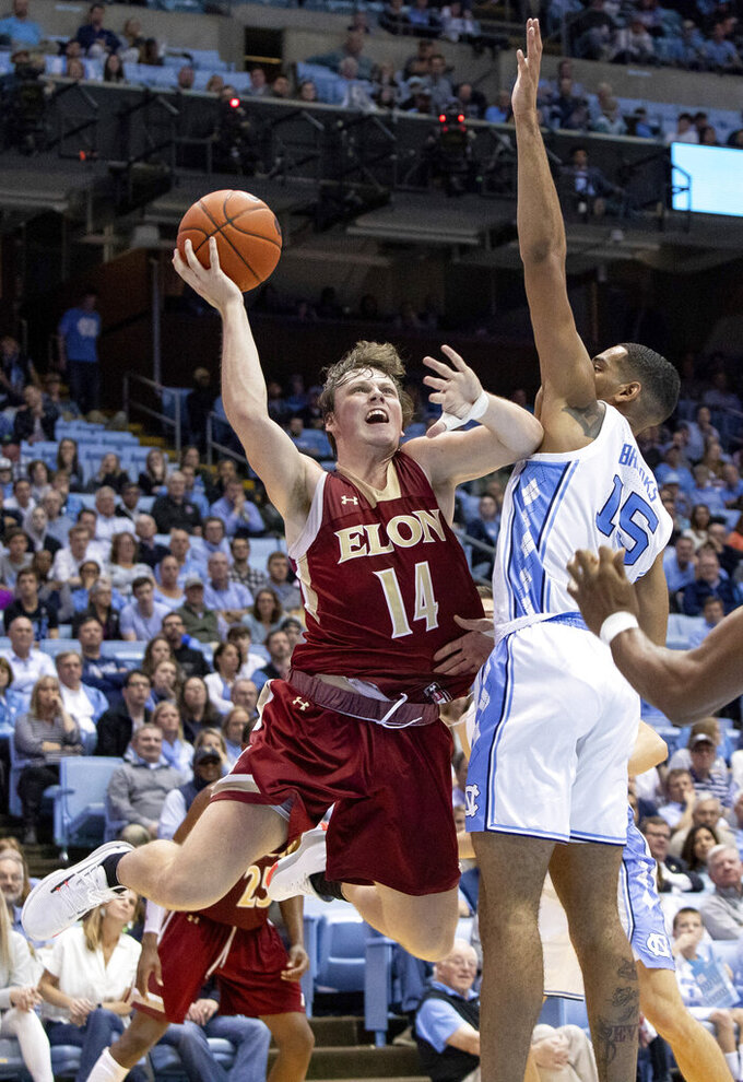 Elon's Zac Ervin (14) attempts a shot as North Carolina's Garrison Brooks (15) defends during the second half of an NCAA college basketball game in Chapel Hill, N.C., Wednesday, Nov. 20, 2019. (AP Photo/Ben McKeown)