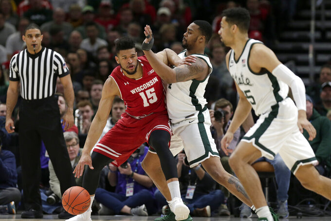 Wisconsin's Charles Thomas IV (15) derives against Michigan State's Nick Ward during the first half of an NCAA college basketball game in the semifinals of the Big Ten Conference tournament, Saturday, March 16, 2019, in Chicago. (AP Photo/Kiichiro Sato)