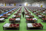 An Iranian army soldier walks past rows of beds at a temporary 2,000-bed hospital for COVID-19 coronavirus patients set up by the army at the international exhibition center in northern Tehran, Iran, on Thursday, March 26, 2020. (AP Photo/Ebrahim Noroozi)