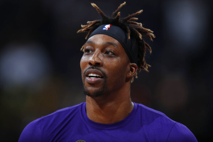 FILE - In this Feb. 12, 2020, file photo, Los Angeles Lakers center Dwight Howard looks on in the first half of an NBA basketball game against the Denver Nuggets in Denver. The mother of Howard's 6-year-old son died nearly six weeks ago due to an epileptic seizure, the Lakers center says. Howard has spent his hiatus from basketball dealing with the difficult task of explaining Melissa Rios' death to their son, but also grateful for the chance to heal from the loss outside the daily grind of the NBA schedule. (AP Photo/David Zalubowski, File)