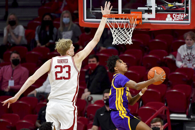 LSU guard Eric Gaines (25) drives past Arkansas forward Connor Vanover (23) top score during the first half of an NCAA college basketball game in Fayetteville, Ark. Saturday, Feb. 27, 2021. (AP Photo/Michael Woods)