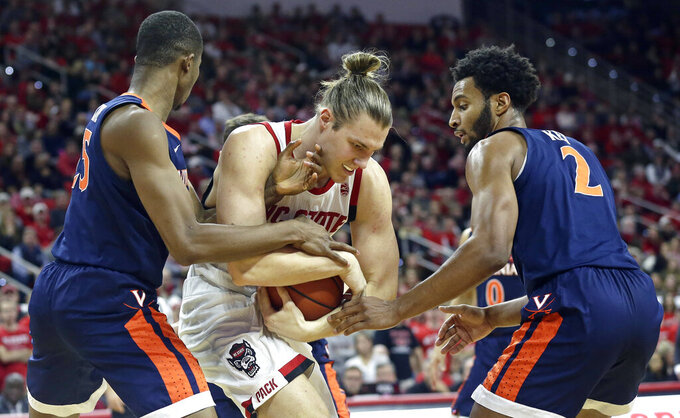 Virginia's Mamadi Diakite, left, and Braxton Key (2) pressure North Carolina State's Wyatt Walker during the first half of an NCAA college basketball game in Raleigh, N.C., Tuesday, Jan. 29, 2019. (AP Photo/Gerry Broome)