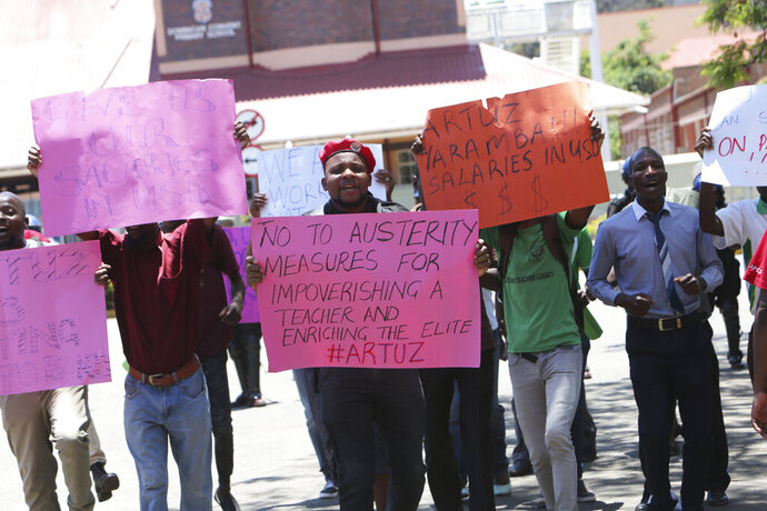 A group of government workers hold placards while protesting in Harare, Wednesday, Nov, 6, 2019. Zimbabwe police Wednesday blocked government workers from marching to protest for better salaries, a day after dozens of public hospital doctors were fired for striking for more pay. (AP Photo/Tsvangirayi Mukwazhi)