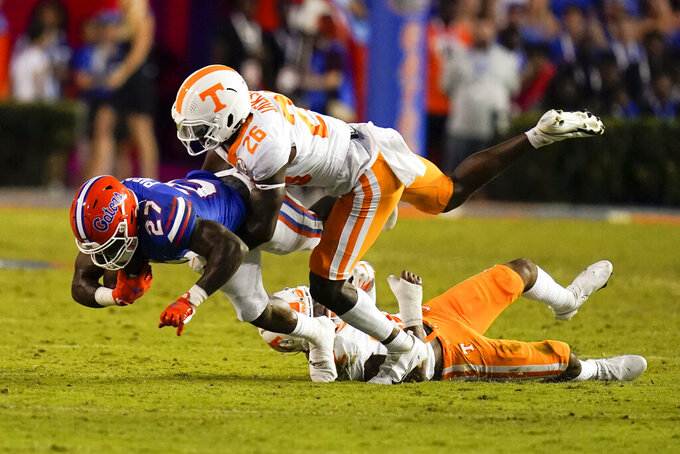 Florida running back Dameon Pierce (27) is brought down by Tennessee defensive back Theo Jackson (26) and defensive back Jaylen McCollough, lower right, during the first half of an NCAA college football game, Saturday, Sept. 25, 2021, in Gainesville, Fla. (AP Photo/John Raoux)