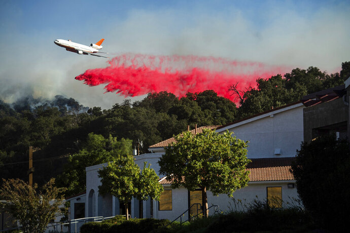 An air tanker drops retardant behind the Newhall Church of the Nazarene while battling the Saddleridge Fire in Newhall, Calif., on Friday, Oct. 11, 2019. The wildfire is raging along the northern border of Los Angeles as powerful Santa Ana winds sweep Southern California. (AP Photo/Noah Berger)