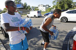 FILE- In this Aug. 12, 2019 file photo, volunteer Matthew Tiggs, left, helps Newark resident Mack Mayton load cases of bottled water into the trunk of his car in Newark, N.J., after Mayton picked it up at the Boylan Street Recreation Center. New Jersey's biggest city has recently been the epicenter of a problem with lead in drinking water, but the United States has an estimated 6 million lead pipes, many of them in unknown locations. (AP Photo/Kathy Willens, File)