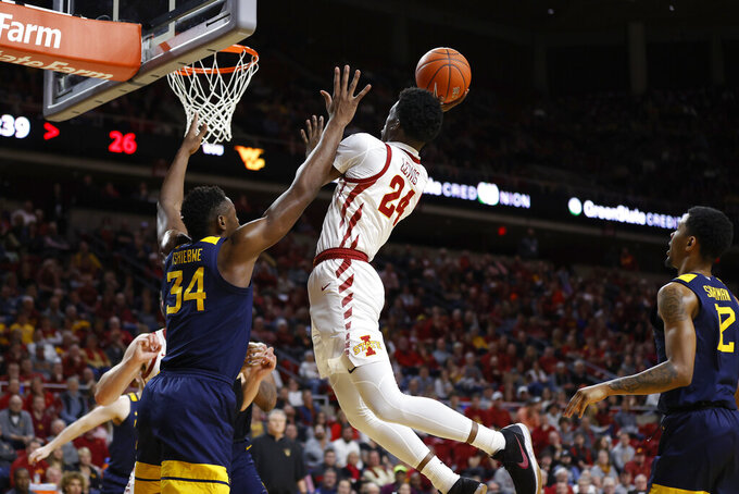 West Virginia forward Oscar Tshiebwe, left, defends against a shot by Iowa State guard Terrence Lewis (24) during the first half of an NCAA college basketball game Tuesday, March 3, 2020, in Ames, Iowa. (AP Photo/Matthew Putney)