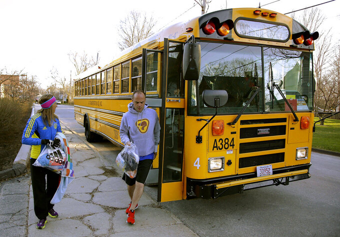 FILE - In this April 21, 2014, file photo, runners in the 118th Boston Marathon disembark a bus as they arrive near the start line in Hopkinton, Mass. Organizers of the marathon, postponed indefinitely because of the coronavirus pandemic, have launched a virtual Athletes' Village in 2020 to reproduce at least some of the camaraderie of the real thing. (AP Photo/Stephan Savoia, File)