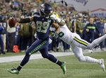 FILE - In this Nov. 15, 2018 file photo, Seattle Seahawks wide receiver Doug Baldwin (89) is tackled by Green Bay Packers defensive back Bashaud Breeland, right, during an NFL football game in Seattle. Baldwin is no longer a football player, and one of his first projects in his post-playing career is spearheading construction of a community center in the Seattle suburb of Renton, Wash. (AP Photo/Elaine Thompson, File)